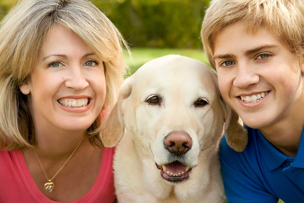 mother and son smiling with dog